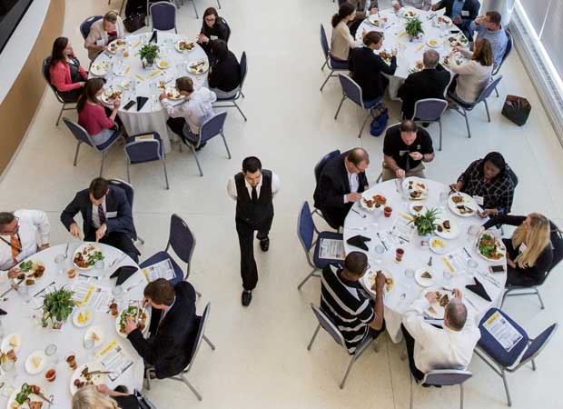 Aerial shot of individuals eating at groups of round tables