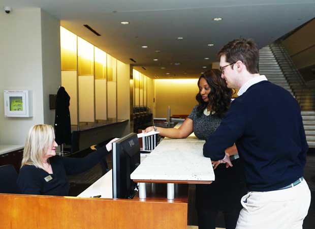 Two attendees at concierge desk receiving help