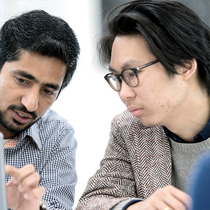 Two male adult learners working on a project in class