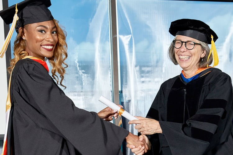 Female student in cap and gown receiving a diploma for an online masters program