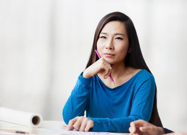 Woman sitting and thinking about her professional goals and how to achieve them.