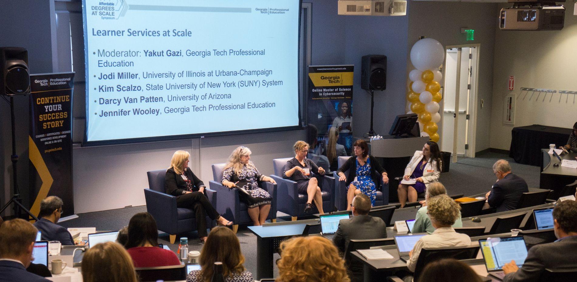 """Yakut Gazimoderates """"Learner Services at Scale"""" panel featuring Jodi Miller (University Illinois at Urbana-Champaign), Kim Scalzo (SUNY), Darcy Van Patten (University of Arizona), and Jennifer Wooley (GTPE)."""