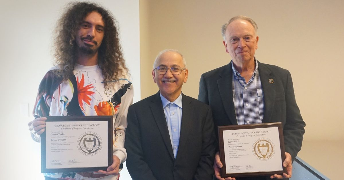 Carson and Terry Tucker with their Power Systems Certificates standing with Professor Sakis